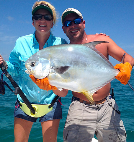 Female and male holding a tuna fish while sports fishing