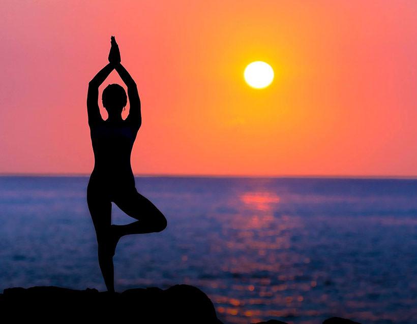 Female doing yoga at sunrise