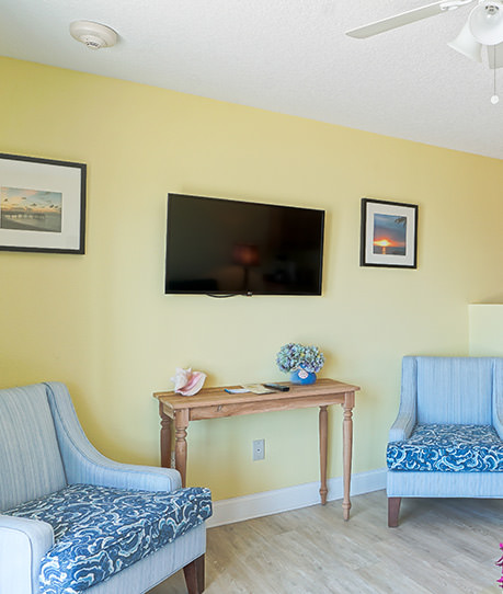 Flat screen tv mounted on wall with two chairs on each side