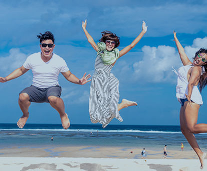 Male and two female friends jump with joy